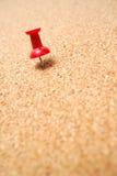 Thumbtack rosso sulla scheda del sughero Fotografia Stock Libera da Diritti