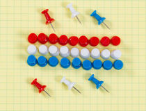 Thumbtacks and graph paper in USA flag colors Stock Photos