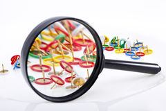 Thumbtacks through magnifier. Colorful thumbtacks through magnifier stock photography