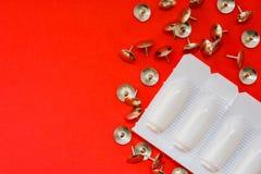 Thumbtacks, odbytniczy suppositories w kocowaniu na czerwonym tle Medyczny pojęcie znak i objawy hemoroid czerwień i szpilki zdjęcie stock