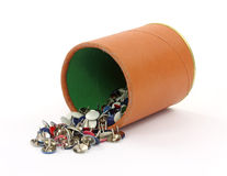 Thumbtacks spilling from cup Royalty Free Stock Image