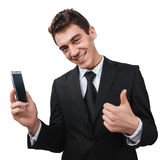Thumbup. A young businessman giving a thumbup to something on his smartphone and smiling Royalty Free Stock Photo