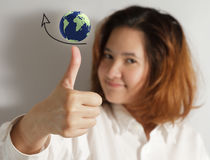 Thumps up. Businesswoman holding thumps up with high grow arrow sign with globe Royalty Free Stock Image