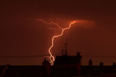Thunder lightning over the city rooftops. At night Royalty Free Stock Photography