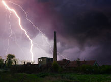 Thunder, lightning and storm over abandoned factory in summer Stock Photos