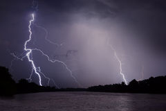 Thunder, lightnings and rain during storm over river and forest Royalty Free Stock Photography