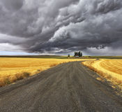 Thunder-storm above Montana. Fields after harvest and road Stock Photos