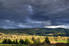 Thunder Storm Landscape. Thunder storm over a green mountain landscape with trees Royalty Free Stock Images