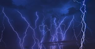 Thunder storm lightning strike on the dark cloudy sky background at night. stock photos