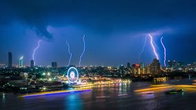 Thunder storm lightning strike on the dark cloudy sky over business building area in Bangkok,Thailand Stock Photo