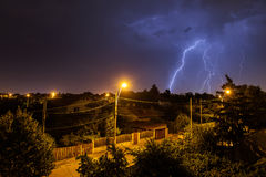 Thunder storm over houses in country side in the middle of the n. Ight with beautiful lightning in background Stock Photo