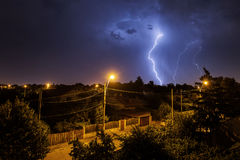 Thunder storm over houses in country side in the middle of the n Royalty Free Stock Image