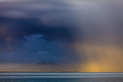 Thunder storm with rain lit by the sun Royalty Free Stock Photo