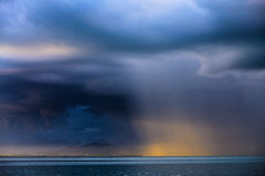 Thunder storm with rain lit by the sun Stock Image