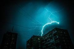 Thunderbolt over the house and dark stormy sky on the background. Royalty Free Stock Photography
