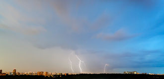Thunderbolts in dark blue sky over city Stock Images