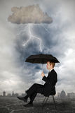 Thundercloud. Businessmann sits with an umbrella under a thundercloud with lightning Stock Images