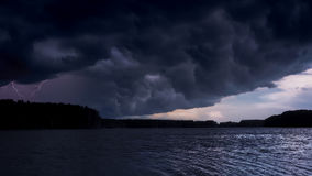 Thundercloud overshadows the sun. Stormy sky over the evening river lake Stock Photography