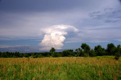 Thundercloud. The photo shows a cumulonimbus storm cloud. It announces the arrival of a violent storm. At the bottom of the frame is a meadow covered with green Royalty Free Stock Images