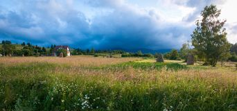 Rural landscape with haystacks in a summer sunny day. Rural mountain landscape with storm clouds. Royalty Free Stock Image