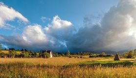 Rural landscape with haystacks in a summer sunny day. Rural mountain landscape with storm clouds. Thunderstom under field. House in the field of golden wheat royalty free stock photos