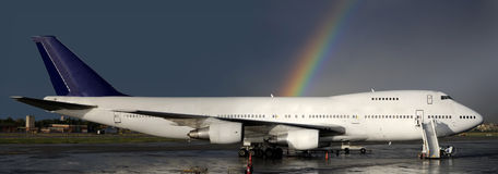 After the thunderstorm. Aircraft parked with a rainbow behind Royalty Free Stock Images