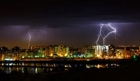 Thunderstorm in the city with lightnings. Thunderstorm in Irkutsk city with few lightnings in dark sky near Angara river Stock Photo