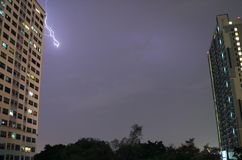 Thunderstorm in the City!! Real Lightning Flashing over the High Buildings in Night Sky of Bangkok. Thailand Stock Photo