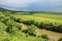 Thunderstorm and dark thunderstorm clouds over the field and the river. stock image