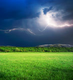 Thunderstorm in green meadow. Thunderstorm with lightning  in green meadow. Nature composition Royalty Free Stock Image