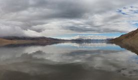 Thunderstorm on the high Tibetan mountains of Lake Tso Moriri, blue water with reflection of gray clouds sky and brown strip dista. Thunderstorm on high Tibetan Royalty Free Stock Images