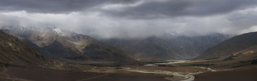 Thunderstorm in the highland river valley of Zanskar: heavy gray clouds fall on peaks, the gloom envelops the hills, panoramic pho Royalty Free Stock Photos
