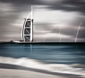 Thunderstorm and lightning on Dubai beach. DUBAI, UAE - NOV 21: Burj Al Arab is 321m, second tallest hotel in the world, luxury hotel stands on an artificial Royalty Free Stock Images
