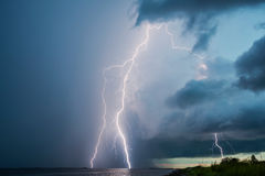 Thunderstorm lightnings. Thunderstorm lightning streaks over the sea with clouds in the evening Stock Photos