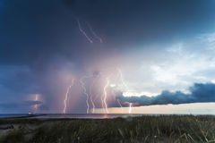 Thunderstorm lightnings 2. Thunderstorm lightning streaks over the sea with clouds in the evening Royalty Free Stock Image