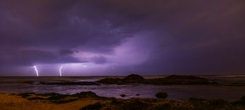 Thunderstorm on mediterranean sea beach. Lightning, heavy clouds and rain stormy weather royalty free stock photography