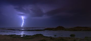 Thunderstorm on mediterranean sea beach. Lightning, heavy clouds and rain stormy weather stock images
