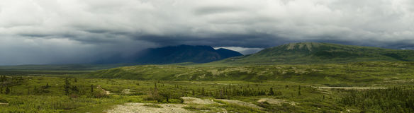 Thunderstorm mountain panorama. Large thunderstorm cloud covering mountain tops in Alaska range Stock Image