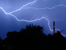 Thunderstorm at night. Here you can see a lightning at night and a power plant. So on this picture natural electricity is meeting human made electricity royalty free stock photo