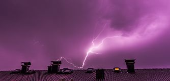 Thunderstorm in the night: Lightning over a roof of a building. Lightning on the colored sky, roof of a building thunderstorm energy house electricity nature stock photo