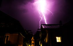 Thunderstorm in the night: Lightning on the sky, neighbourhood, Austria. Powerful Lightning on the cloudy sky, building in foreground, Austria thunderstorm stock image