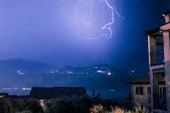 Thunderstorm in the night: Lightning on the sky, neighbourhood, Italy. Lightning on the cloudy sky, mountains and lake, building in foreground, Italy stock photos