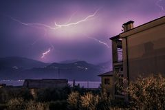 Thunderstorm in the night: Lightning on the sky, neighbourhood, Italy. Lightning on the cloudy sky, mountains and lake, building in foreground, Italy stock photography