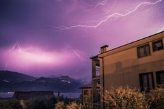 Thunderstorm in the night: Lightning on the sky, neighbourhood, Italy. Lightning on the cloudy sky, mountains and lake, building in foreground, Italy stock images