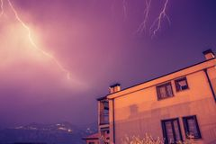 Thunderstorm in the night: Lightning on the sky, neighbourhood, Italy. Lightning on the cloudy sky, mountains and lake, building in foreground, Italy stock photo
