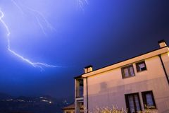 Thunderstorm in the night: Lightning on the sky, neighbourhood, Italy. Lightning on the cloudy sky, mountains and lake, building in foreground, Italy royalty free stock photography