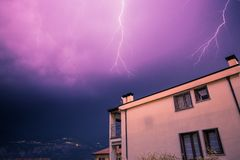 Thunderstorm in the night: Lightning on the sky, neighbourhood, Italy. Lightning on the cloudy sky, mountains and lake, building in foreground, Italy royalty free stock images