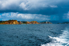 Thunderstorm off the Coast of St. Thomas. Rock formation in Caribbean Sea off the cost of St. Thomas in the Virgin Islands.  Thunderstorm is chasing the boat Stock Photography