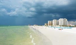 Thunderstorm over beautiful white sand beach in Florida. Buildings, hotels and beach chairs and parasols on white sand. Gulf of Mexico, Clearwater Beach royalty free stock images