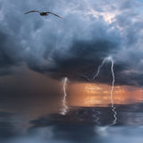 Thunderstorm over ocean. Thunderstorm with rain and lightning over ocean, majestic clouds in the sky Stock Photo